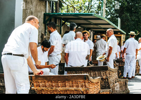Monte, Madeira, Portugal - Sep 14, 2019: Wicker Basket Sledges drivers, Carreiros do Monte. Traditional mean of transport to Funchal, now a tourist attraction. Typical straw hats, white clothes. - Stock Photo