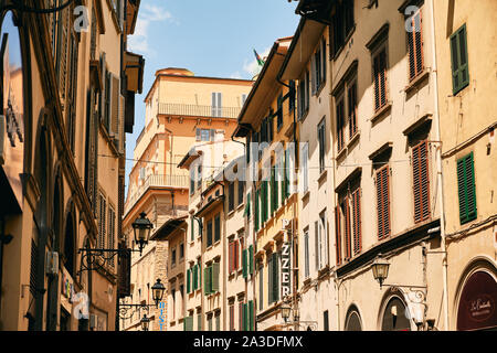 Shabby houses with shops and cafes located on narrow street of old town on sunny day in Tuscany, Italy - Stock Photo