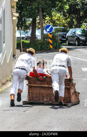 Monte, Madeira, Portugal - Sep 14, 2019: Wicker Basket Sledge ride with Carreiros do Monte. Traditional mean of transport to Funchal, now a tourist attraction. People riding downhill with drivers. - Stock Photo