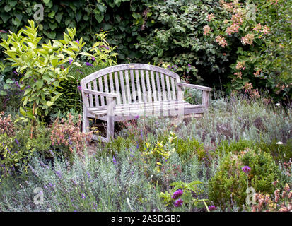 A wooden park bench rests in a garden of fall grasses and wild flowers in a lovely Michigan USA scene - Stock Photo