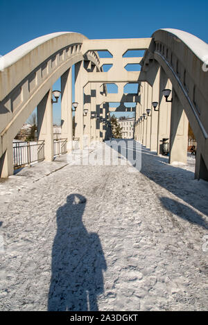 concrete bridge over Olse river in Karvina - Darkov town in Czech republic during winter day with clear sky and bit of snow and with photographer shad - Stock Photo