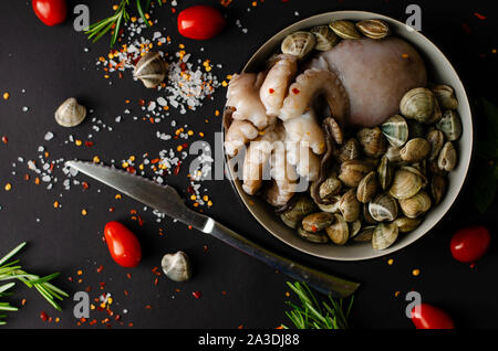 A bowl with fresh octopus with clams and ingredients for cooking on a black background with a space for text. top view