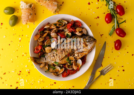 Mediterranean food concept. Bream and clams with tomatoes cherry,olive bread and rosemary on yellow baclground.Flat lay, copy space