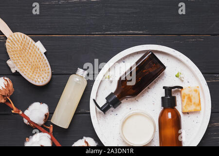 Organic natural herbal cosmetics on black wooden background. - Stock Photo