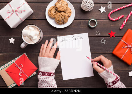 Woman writing letter to Santa with wishes - Stock Photo