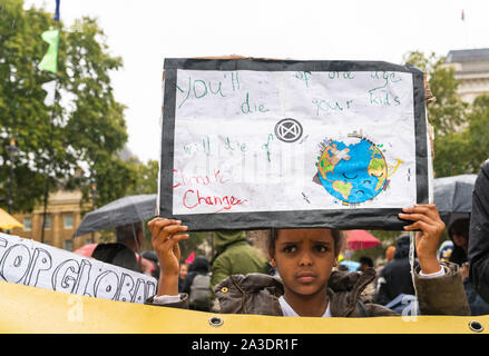 7th Oct 2019 - London, UK. A young climate change activist holds the banner at Extinction Rebellion protest in London. - Stock Photo