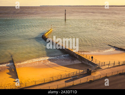 Water breakers casting shadows onto the golden beach in the late afternoon sun on the west cliff beach in Ramsgate, Kent UK. - Stock Photo