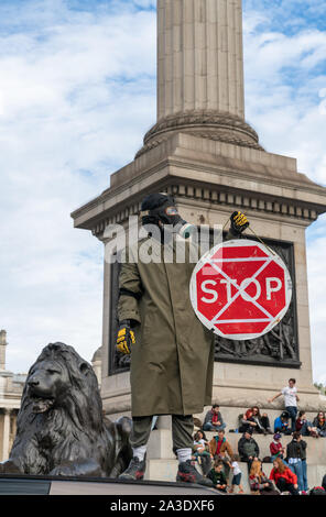 7th Oct 2019 - London, UK. A protester wearing a gas mask on top of a car blocking the road in Trafalgar Square. - Stock Photo