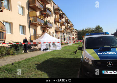 07 October 2019, Frankfurt/Oder: Policemen line up at a house where two dead men have been found. Homicide's investigating. A 52-year-old had fallen from the fourth floor of a residential building early Monday morning, said a spokeswoman for the Brandenburg control center this evening. Rescue workers tried to revive him. It is assumed that he died as a result of the fall, according to the spokeswoman. The man's father, an 83-year-old senior, was found dead in the apartment in the house. Photo: Jan-Henrik Hnida/MOZ/dpa - Stock Photo