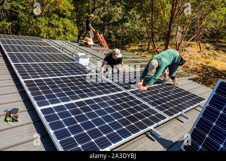Workers install solar photovoltaic panels on a homeowners roof in British Columbia, Canada. - Stock Photo
