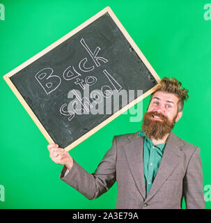 Teacher bearded man holds blackboard with inscription back to school green background. Keep working. Teaching stressful occupation. Teacher with tousled hair stressful about school year beginning. - Stock Photo