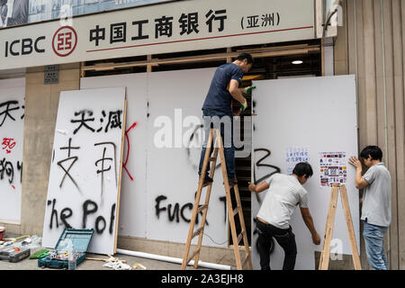 Kowloon, Hong Kong, China,. 7 October, 2019. After a night of violent confrontations between police and pro-democracy protestors in MongKok and YauMaTei in Kowloon, many MTR railway stations and what are thought to be pro-Beijing business franchises were vandalised. Workers fitting hoardings to protect Chinese ICBC Bank - Stock Photo