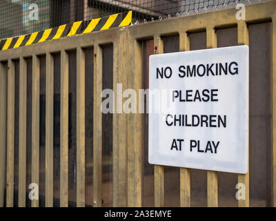 No smoking please, children at play sign on fence at recreational playground area - Stock Photo