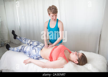 Physiotherapist giving a treatment to a female client - Stock Photo