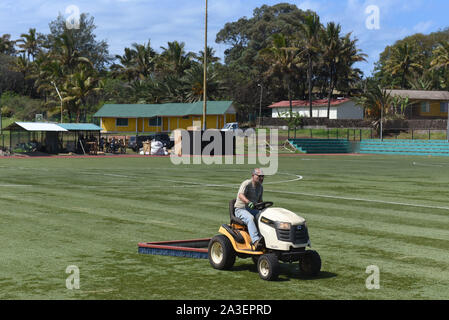 A groundsman cuts the grass with a mower ride on a sports field.Hanga Roa is the capital of Easter Island, a Chilean island in the southeastern Pacific Ocean. The village has around 5,000 inhabitants, which comprises between 87 and 90 percent of the total population of the island. Excluding a small percentage still engaged in traditional fishing and small-scale farming, the majority of the population is engaged in tourism which is the main source of income. - Stock Photo