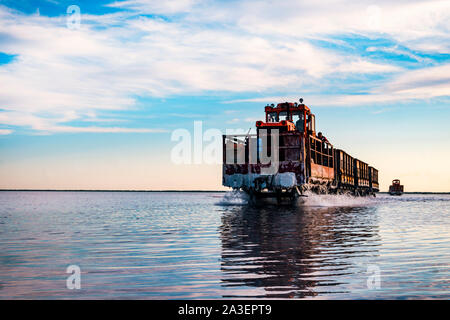 Old train rides on the railway laid in the water through the salt lake. train travels from water. Mined salt in Lake Burlin. Altai. Russia. Bursolith. - Stock Photo