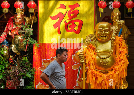 Outside a shop for Buddhist objects in Waterloo St., Bugis area, Singapore, a man passes between statues of the Monkey King and the Laughing Buddha - Stock Photo