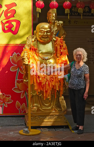 Outside a shop for Buddhist objects in Waterloo St., Bugis area, Singapore, a woman poses next to a statue of the Laughing Buddha (Budai or Hotei) - Stock Photo