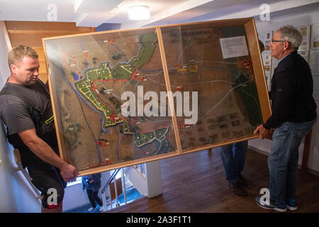 19 September 2019, Saxony-Anhalt, Abbenrode: Christoph Weihe (l.) and Lothar Engler (r.) carry a model into the Heimatmuseum Abbenrode, where the border fortifications of the GDR can be seen in the section Lüttgenrode and Rimbeck. One guarded the border in the east, the other in the west. They knew a lot about each other, but not everything, they say today. For several years ex-limiters have been meeting regularly in the Harz mountains. (to dpa 'They endure contrasts - former border guards from East and West meet ') Photo: Klaus-Dietmar Gabbert/dpa-Zentralbild/dpa - Stock Photo