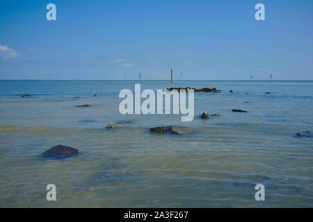 View over the North Sea (mud flats / shallows) near Dornumer Siel towards the friesian island Langeoog - Stock Photo