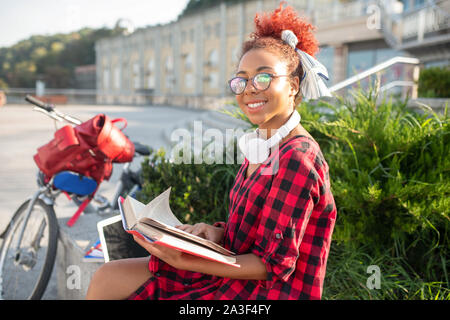 Student feeling inspired while reading interesting book - Stock Photo