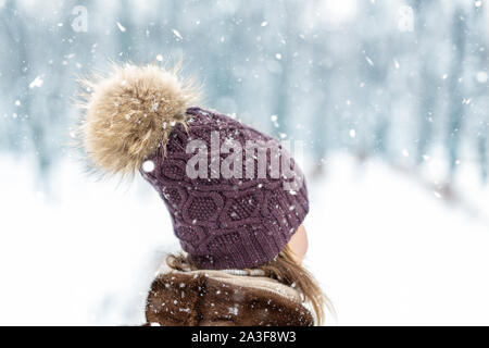 Close-up back view of young adult woman head wearing warm stylish woolen knitted handmade hat with big fluffy natural fur pompon. walking at city park - Stock Photo