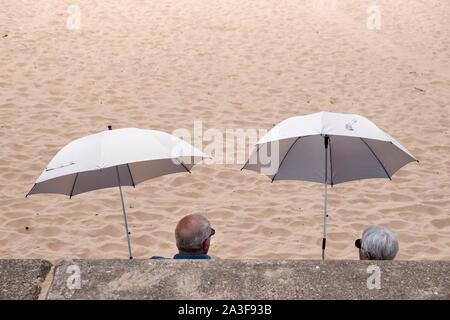 An old couple sitting on a sandy beach under umbrellas. - Stock Photo