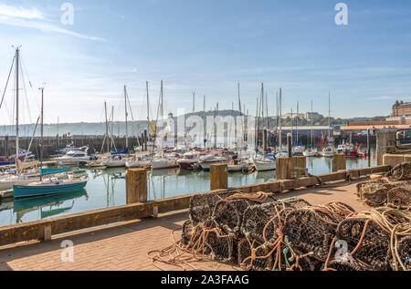A marina lies beside a pier with a lighthouse and a wharf with a trawler is opposite. Lobster pots are in the foreground and a hill with hotels is in - Stock Photo