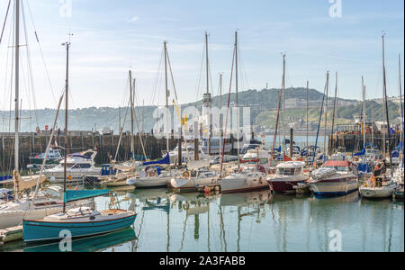 A marina of yachts and motor-boats lies beside a pier with a lighthouse. A hill with hotels is in the far distance and a blue sky is overhead. - Stock Photo