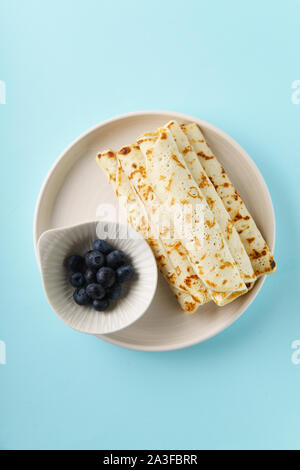 Rolled pancakes with blueberry on blue background with text space - Stock Photo