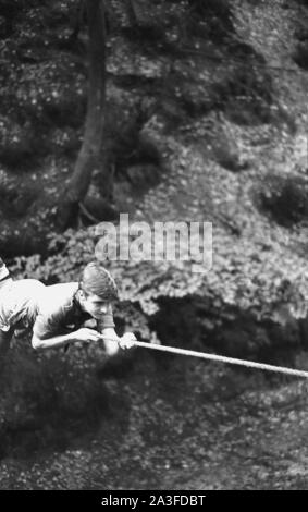 1960s, historical, a scout using his hands and feet on a rope to manoeuvre himself over a crossing in a forest, England, UK. - Stock Photo