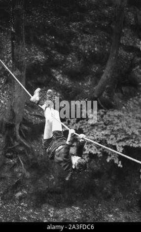 1960s, historical, a scout using his hands and feet while hanging on a rope to manoeuvre himself over a crossing in a forest, England, UK. - Stock Photo