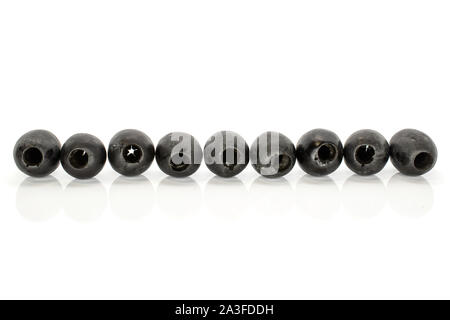 Group of nine whole tasty black olive in line isolated on white background - Stock Photo