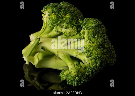 Lot of whole fresh green broccoli isolated on black glass - Stock Photo
