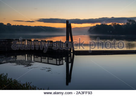 Early Fall shot of Ferry Park in Rocky Hill CT at sunrise with mist on the Connecticut River. - Stock Photo