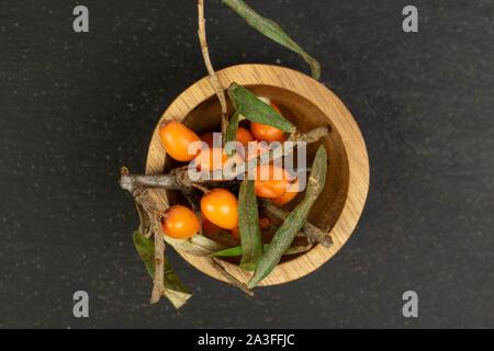 Lot of whole fresh ripe orange sea buckthorn berry in bamboo bowl flatlay on grey stone - Stock Photo