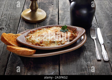 Casserole with potatoes, meat and cheese. Served in a baking dish. - Stock Photo