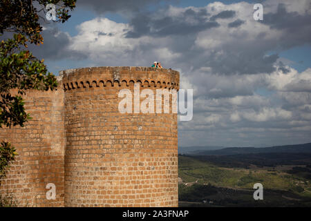 Tourists taking a picture from the top of a tower in the Fortezza Albornoz in Orvieto on a cloudy summer evening. - Stock Photo