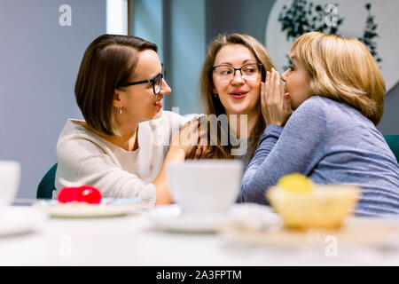gossips with best friends horizontal shot of two beautiful women whispering to their third friends ears while drinking coffee with cakes in cafe 2a3fptm