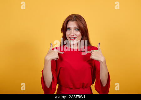 Smiling woman using gestures shows at herself with index fingers of both hands. - Stock Photo