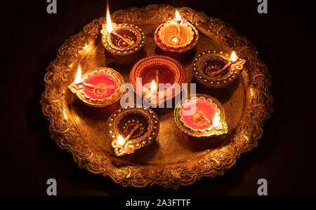 Happy Diwali. Clay diya candles illuminated in Dipavali, Hindu festival of lights. Traditional oil lamps on dark background - Stock Photo