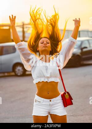 Sunset warm light backlight throwing long hair upwards fanciful young woman wearing White Summer clothing three-quarter length facing camera frontal - Stock Photo
