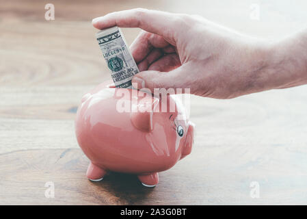 close-up of male hand putting folded dollar bill in pink piggy bank on wooden table, home finance and saving money concept - Stock Photo