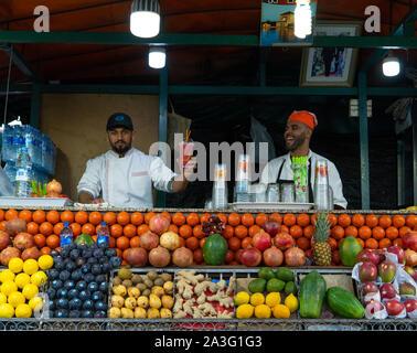 Marrakech, Morocco - 15 JAN 2019: Two happy arabic Fruit fresh juice sellers on Jemma El Fna square in Marrakesh, Morocco