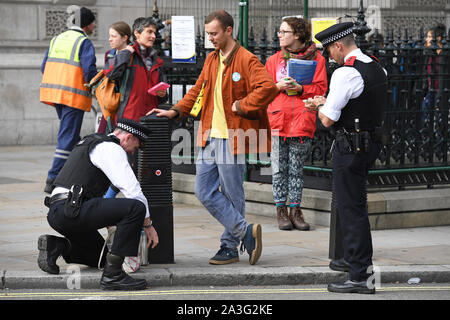 An Extinction Rebellion (XR) protester has his bag searched by police in Parliament Square, Westminster, London, as the climate change protest continued into a second day.