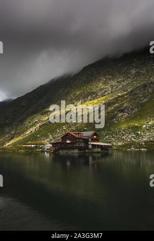Fagaras, Romania - August 21 2019 :  Spectacular view of Balea lake mountain chalet next to Balea glacial lake in the Carpathian mountains on a foggy - Stock Photo