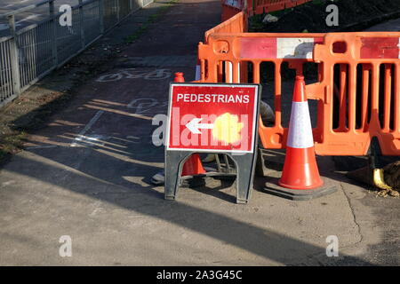 Camberley, Surrey, UK - February 6 2018: Sign telling pedestrians walking on the pavement or sidewalk to take a diversion around some road works maint - Stock Photo
