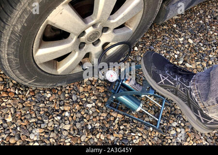 Camberley, Surrey, UK - February 25 2018: Man's foot pumping up a flat car tyre or tire, which is deflated - Stock Photo