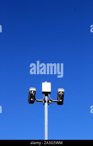 Upright view of security cameras on tall pole against deep blue sky