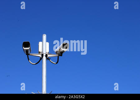 Landscape view of security cameras on tall pole against deep blue sky